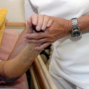 En sjuksköterska håller en patients hand. Implementering av digitalisering i vården kan ta tid