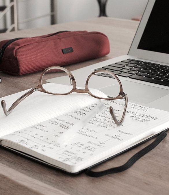 finansieringssystem bild på glasögon, papper och ett anteckningsblock